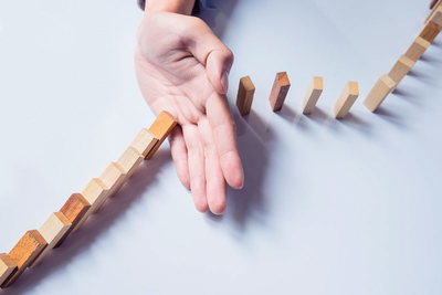 Business Continuity Plan: hands stopping domino