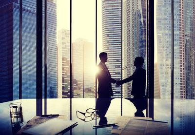 business-agreement-two-people-shaking-hands-in-front-of-tall-windows